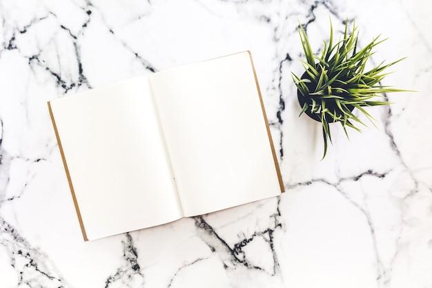 Bovenaanzicht van werkruimte en geopende notebook met mock up blanco pagina's Premium Foto