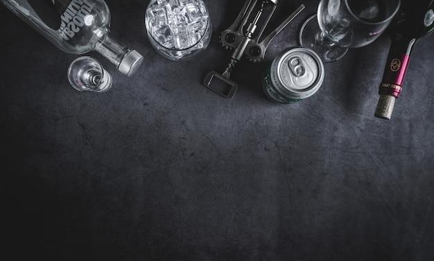 Bovenaanzicht van wijnfles, wodka fles, ijsblokje, bier en kurkentrekker Premium Foto