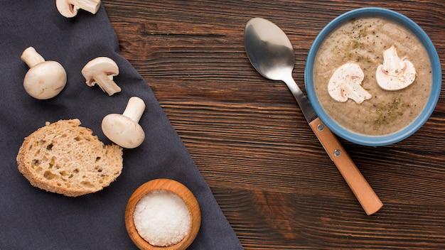 Bovenaanzicht van winter champignonsoep in kom met lepel en brood Gratis Foto