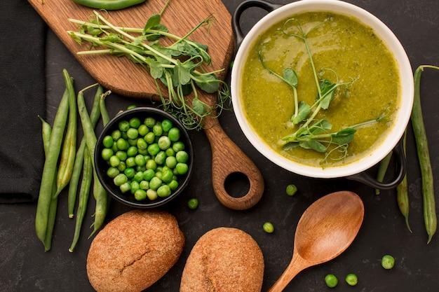 Bovenaanzicht van winter erwten soep met brood en lepel Gratis Foto