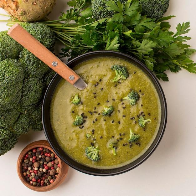 Bovenaanzicht van winterbroccolisoep in kom met lepel en selderij Gratis Foto