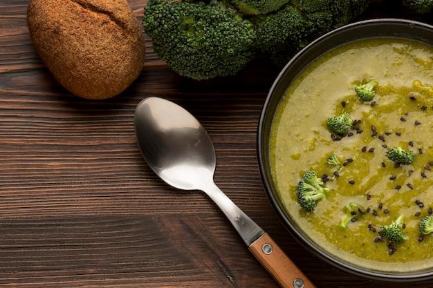 Bovenaanzicht van winterbroccolisoep met lepel en brood Gratis Foto