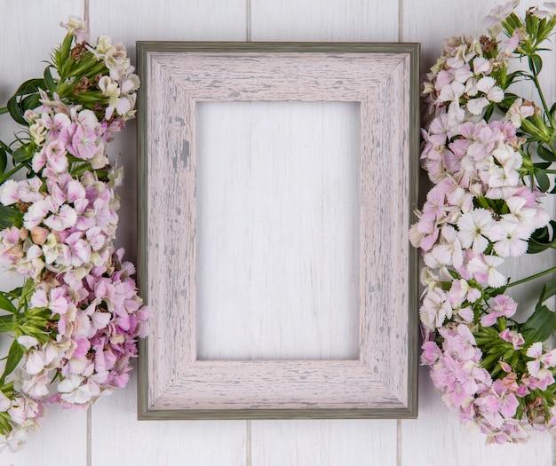 Bovenaanzicht van wit frame met bloemen op een wit oppervlak Gratis Foto
