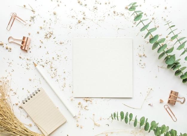 Bovenaanzicht van wit papier op werktafel met mock-up accessoires en droge bloem. Premium Foto
