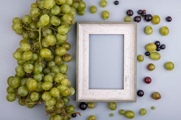 Bovenaanzicht van witte druif en frame met druivenbessen op grijze achtergrond met kopie ruimte Gratis Foto