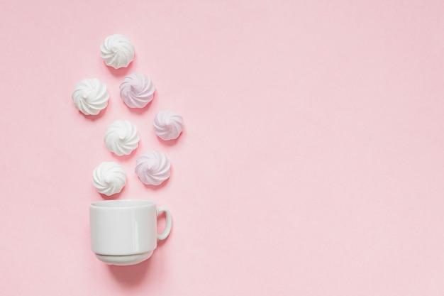Bovenaanzicht van witte en roze gedraaide schuimgebakjes op roze Premium Foto