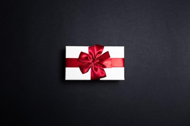 Bovenaanzicht van witte geschenkdoos met rode strik op zwarte ondergrond Premium Foto