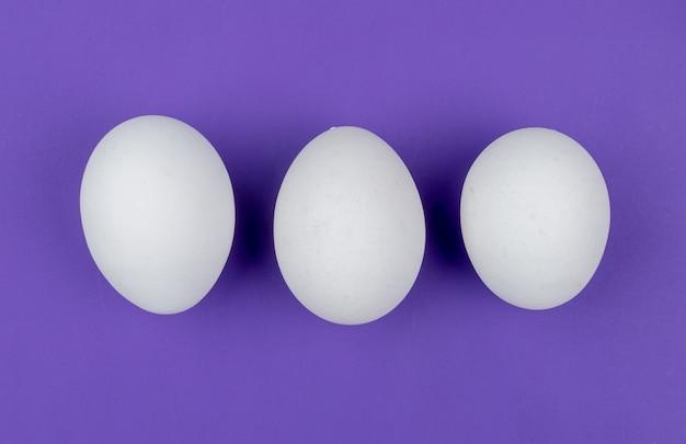Bovenaanzicht van witte verse kippeneieren gerangschikt in een lijn op een violette achtergrond Gratis Foto