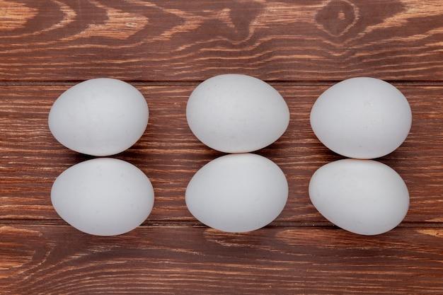 Bovenaanzicht van witte verse kippeneieren gerangschikt op een houten achtergrond Gratis Foto