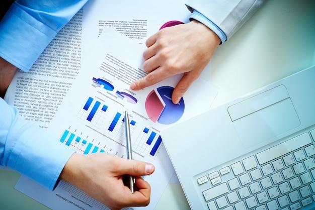 Bovenaanzicht van zakenlieden analyseren staafdiagrammen en een laptop Gratis Foto