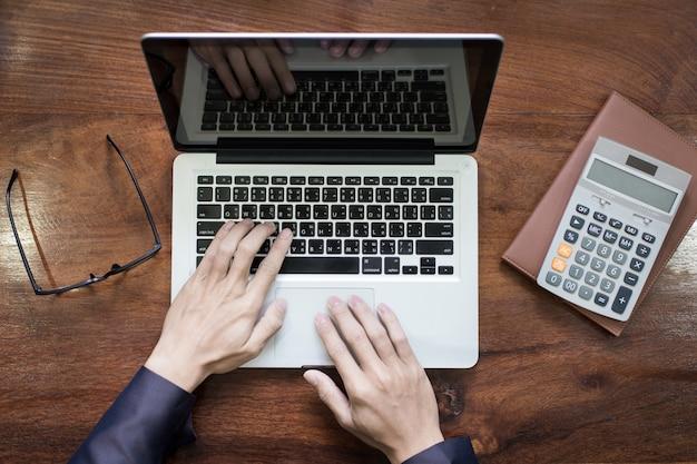 Bovenaanzicht van zakenman handen werken op laptop of tablet pc op houten bureau. Gratis Foto