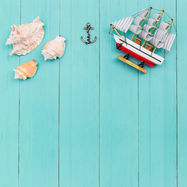Bovenaanzicht van zeeschelpen en speelgoed schip Gratis Foto