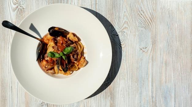Bovenaanzicht van zeevruchten pasta op houten tafel Gratis Foto