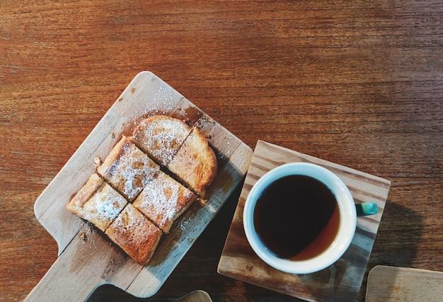 Bovenaanzicht van zoet brood dient op een snijplank met hete thee. leg op houten tafel met kopie ruimte Premium Foto