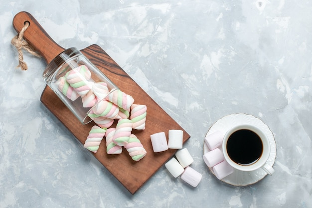 Bovenaanzicht van zoete gekleurde marshmallows met kopje thee op lichte witte ondergrond Gratis Foto
