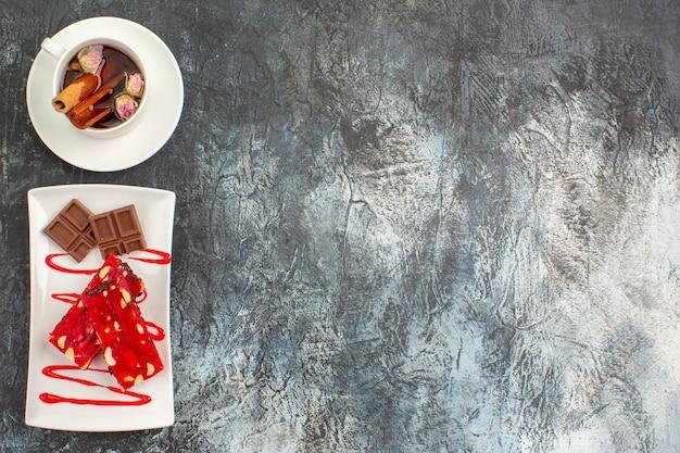Bovenaanzicht van zoete heerlijke chocolaatjes op witte plaat met een kopje kruidenthee op grijze grond Gratis Foto