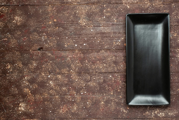 Bovenaanzicht van zwarte cakevorm langgevormd de bruine rustiek, cake eten bak zoet bureau, hout Gratis Foto