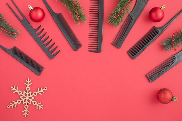 Bovenaanzicht van zwarte kammen en kerstmissamenstelling op rood Premium Foto