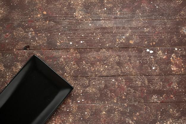 Bovenaanzicht van zwarte lege schimmel geïsoleerd op bruin rustiek, cake voedsel oven hout houten Gratis Foto