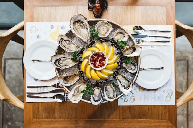 Bovenaanzicht veel soorten verse oesters geserveerd in een ronde lade met schijfje citroen en pikante saus. Premium Foto
