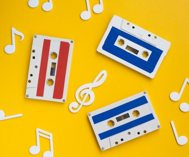 Bovenaanzicht veelkleurige cassettebandjes met decoratieve muzieknoten rond Gratis Foto