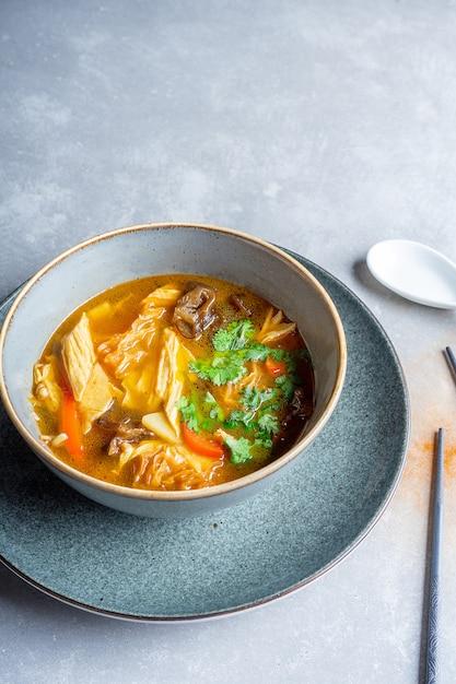Bovenaanzicht veganistische soep met tomaten, noedels, shiitake-paddenstoelen, peterselie en gegrilde tofu-kaas Premium Foto