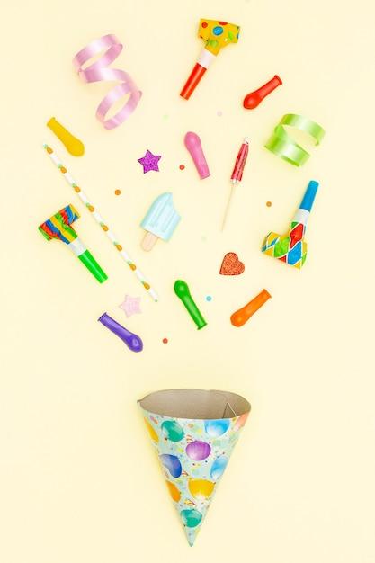 Bovenaanzicht verjaardag arrangement met feestmuts en ballonnen Gratis Foto