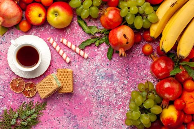 Bovenaanzicht vers fruit samenstelling kleurrijke vruchten met thee en wafels op roze oppervlak Gratis Foto