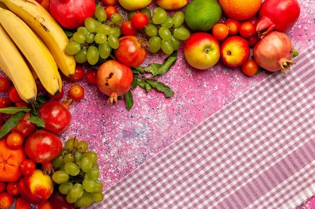 Bovenaanzicht vers fruit samenstelling kleurrijke vruchten op het roze oppervlak Gratis Foto