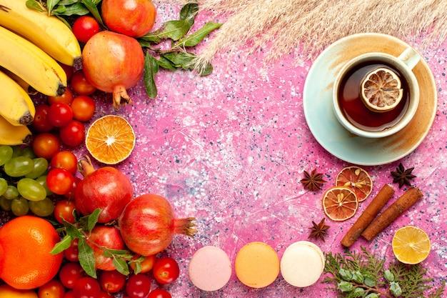 Bovenaanzicht vers fruit samenstelling met franse macarons en thee op lichtroze oppervlak Gratis Foto