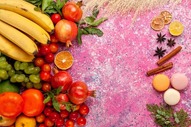 Bovenaanzicht vers fruit samenstelling met franse macarons op lichtroze oppervlak Gratis Foto