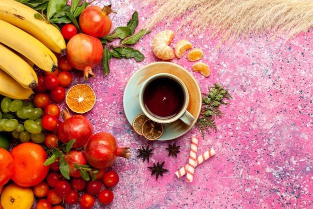 Bovenaanzicht vers fruit samenstelling met kopje thee op het licht roze oppervlak Gratis Foto