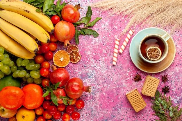 Bovenaanzicht vers fruit samenstelling met wafels en thee op lichtroze oppervlak Gratis Foto
