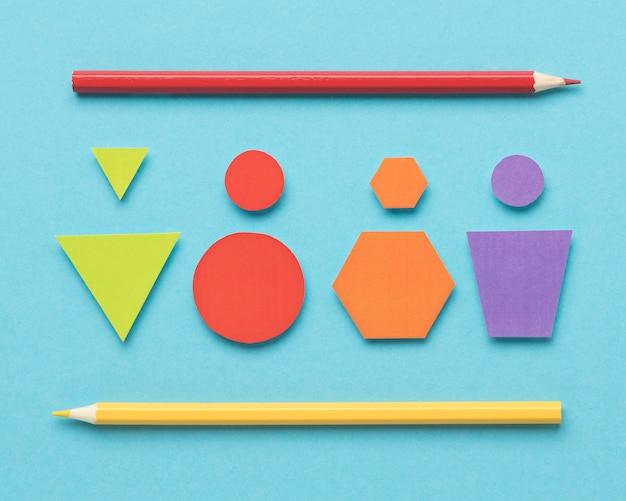 Bovenaanzicht verschillende gekleurde geometrische vormen op blauwe achtergrond Gratis Foto