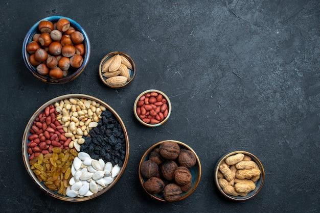 Bovenaanzicht verschillende noten samenstelling van snacks op donkergrijze achtergrond noten snack foto walnoot hazelnoot Gratis Foto