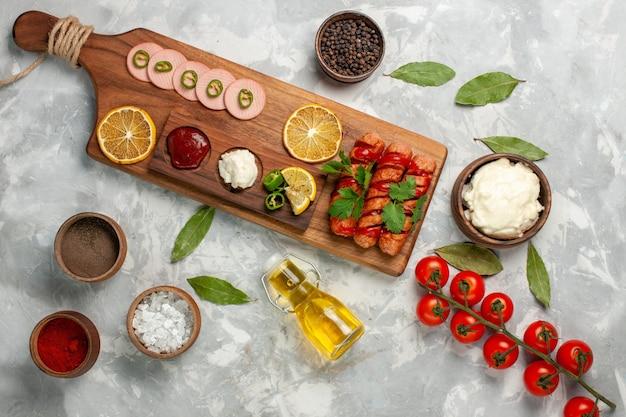 Bovenaanzicht verschillende voedselsamenstelling worstjes met verse tomaten, kruiden, olie en citroenen op lichte tafel maaltijd voedsel veegtable kleurenfoto Gratis Foto