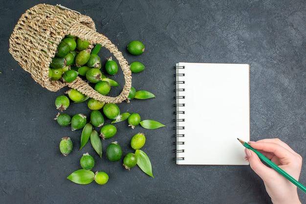 Bovenaanzicht verse feijoas in mandpotlood in vrouwelijke hand op notitieboekje op donkere ondergrond Gratis Foto