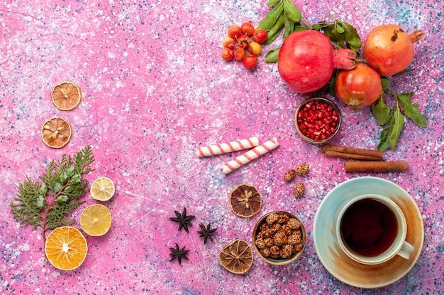 Bovenaanzicht verse granaatappel met groene bladeren en kopje thee op lichtroze oppervlak Gratis Foto