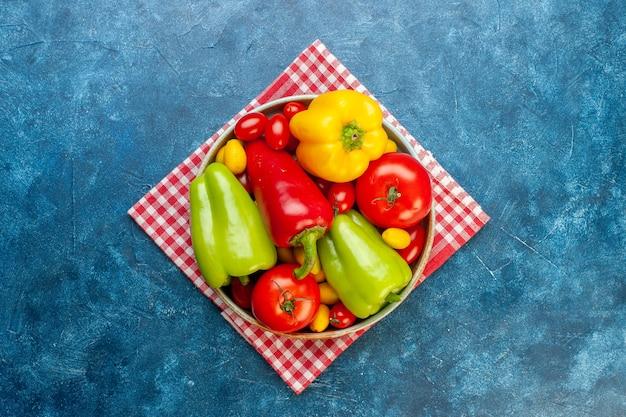 Bovenaanzicht verse groenten cherry tomaten verschillende kleuren paprika tomaten cumcuat op schotel op rood wit geruite keukenhanddoek op blauwe tafel met kopie ruimte Gratis Foto