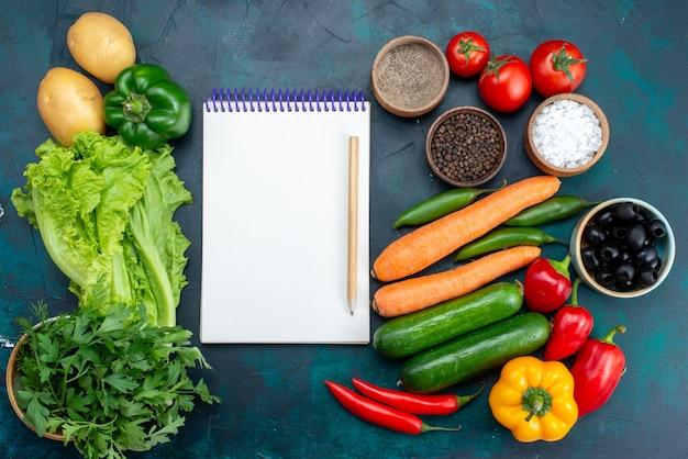Bovenaanzicht verse groenten met greens en blocnote op het donkerblauwe bureau lunch salade snack plantaardig voedsel Gratis Foto