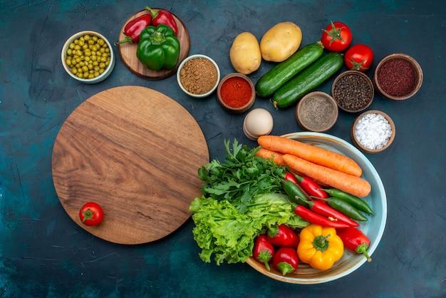 Bovenaanzicht verse groenten met greens en kruiden op het blauwe bureau snack lunch salade plantaardig voedsel Gratis Foto