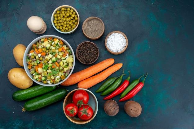 Bovenaanzicht verse groenten met greens groentesalade op blauw bureau lunch salade snack plantaardig voedsel Gratis Foto