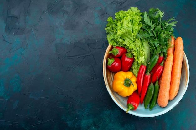 Bovenaanzicht verse groenten met greens op de donkerblauwe vloer lunch salade plantaardig voedsel Gratis Foto