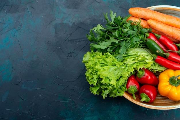 Bovenaanzicht verse groenten met greens op het blauwe bureau snack lunch salade plantaardig voedsel Gratis Foto
