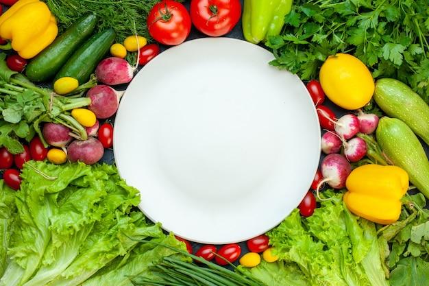 Bovenaanzicht verse groenten peterselie paprika sla dille citroen tomaten radijs witte ronde plaat op donkere ondergrond Gratis Foto