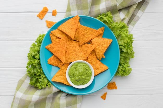 Bovenaanzicht verse guacamole met nacho's op tafel Gratis Foto