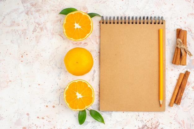Bovenaanzicht verse mandarijnen gesneden mandarijnen kaneelstokjes potlood op notebook op helder geïsoleerd oppervlak met vrije ruimte Gratis Foto