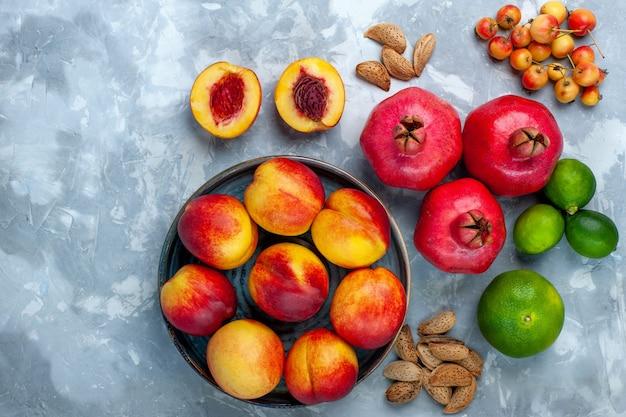 Bovenaanzicht verse perziken heerlijk zomerfruit met mandarijnen en citroen op lichtwit bureau Gratis Foto