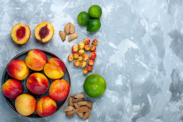 Bovenaanzicht verse perziken heerlijk zomerfruit met mandarijnen op het lichtwitte bureau Gratis Foto