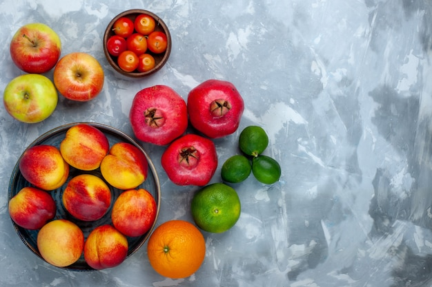 Bovenaanzicht verse perziken heerlijk zomerfruit met pruimen en appels op lichtwit bureau Gratis Foto
